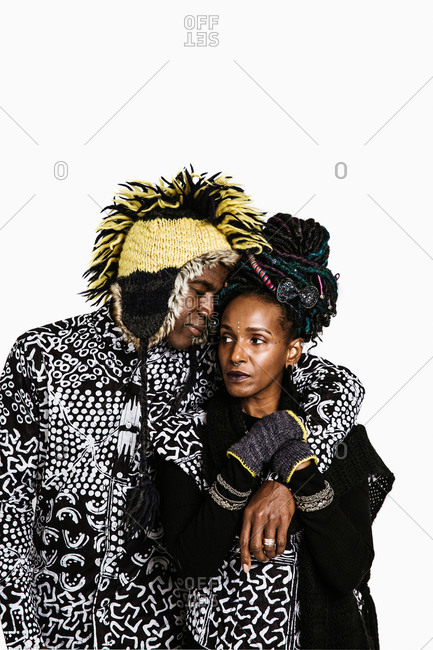 A portrait shot of Black man wearing yellow and black hat embracing woman with piercings and colorful hair