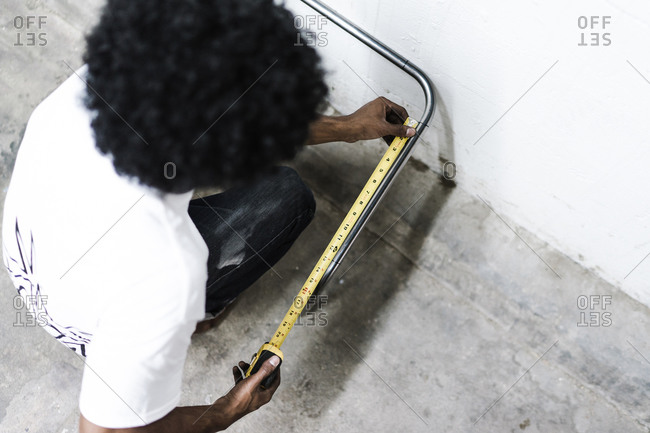 A top angle shot of a man using a measuring tape near a wall