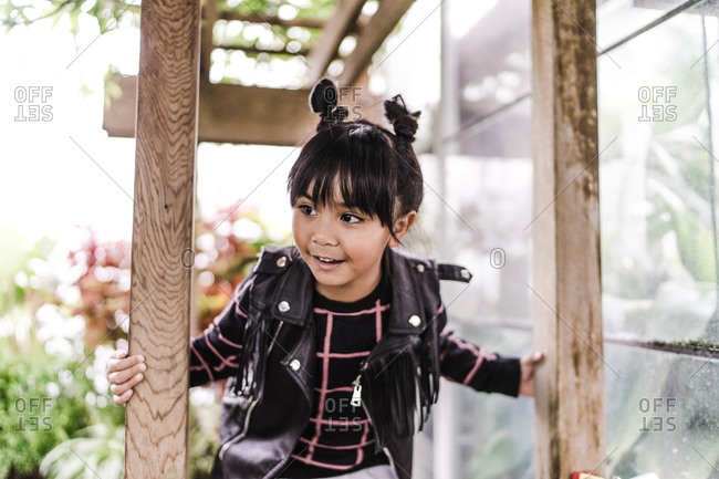 A close up shot of a happy young Asian girl with pigtails playing outside