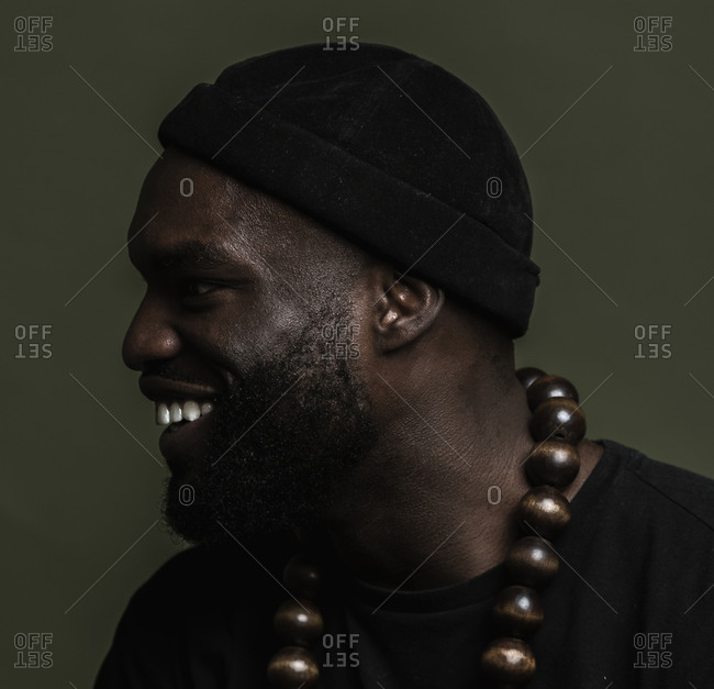 A side profile close up shot of a smiling African American man wearing a black beanie cap posing with a big beads necklace against a green background