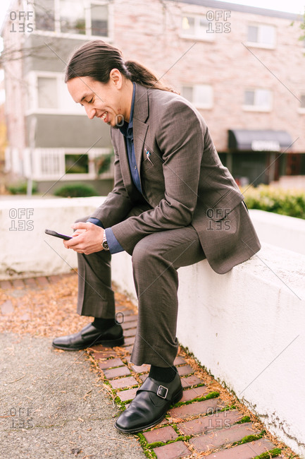 Man wearing suit working on his phone sitting outside