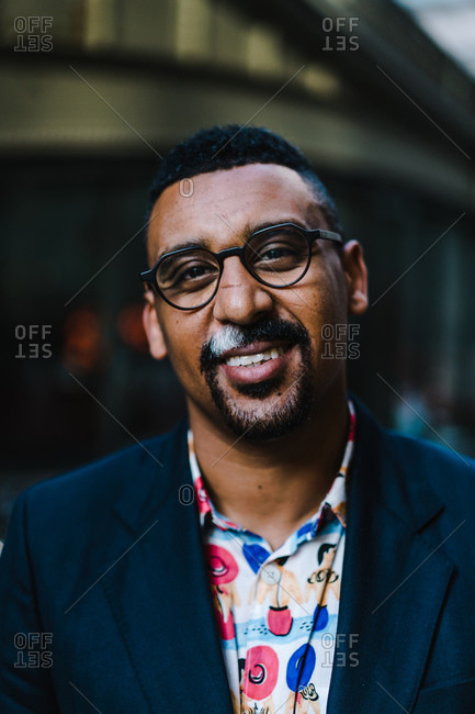 Man with glasses smiling outside in a suit