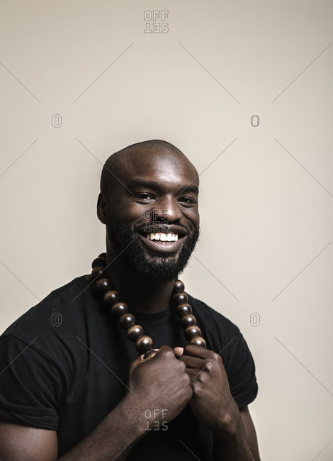 A close up shot of a happy bald African American man with beard posing with a big beads necklace while looking at camera
