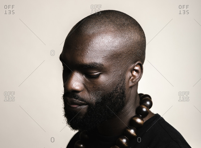 A close up shot of a bald African American man with beard wearing a big beads necklace