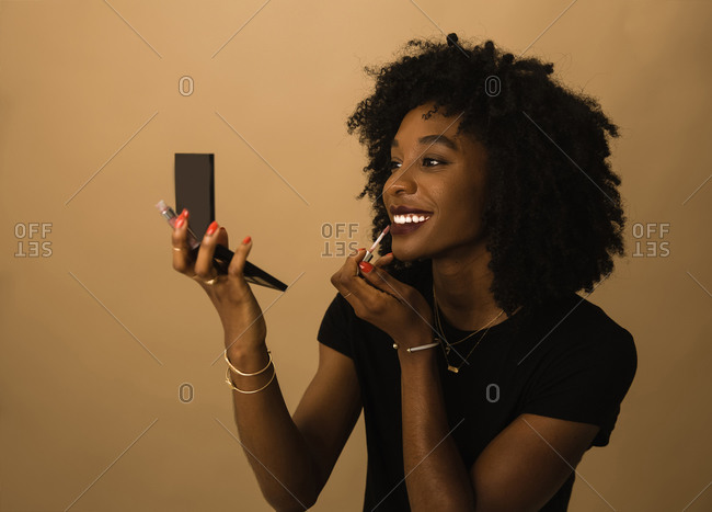 Black woman applying lipstick with a compact mirror in front of brown wall