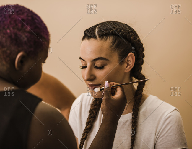 Young Latina woman sitting down as makeup is applied on her