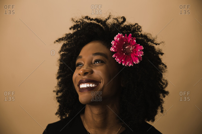 Guyanese woman smiling in front of a brown wall with a flower in her curly hair