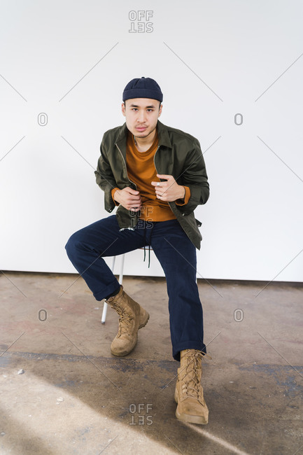 Vertical shot of a handsome Asian man sitting on a chair and looking at the camera