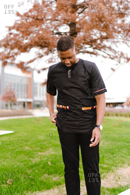 Confident black man in stylish black clothes standing in the park and smiling