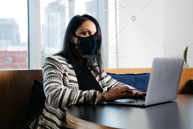 Indian female lawyer typing on a laptop with face mask on and looking at the camera