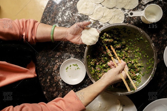 Top view of a Taiwanese senior woman making traditional chicken dumplings