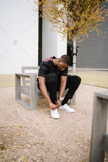 Black man in stylish clothes sitting in a wooden chair and bending over to tie his shoelaces