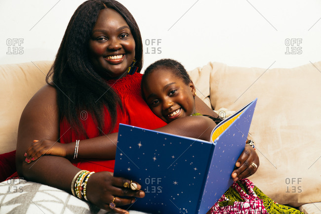 Young girl hugging her black mother who is reading a bedtime stories book for her daughter