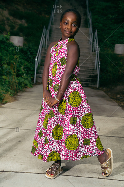Young Black girl wearing a floral dress and posing in front of a stairway in a park outdoors