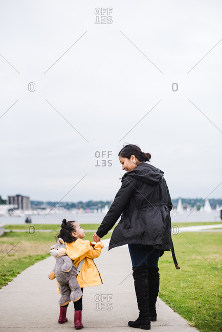 Mother and daughter looking at each other while walking on an empty track holding hands