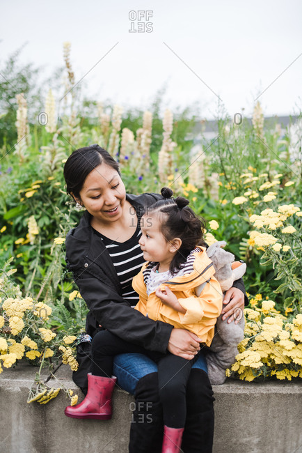 Mother and daughter sitting on a pavement surrounded by flowers