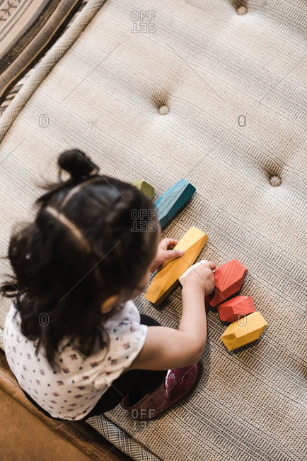 Top shot of a little girl playing with wooden blocks