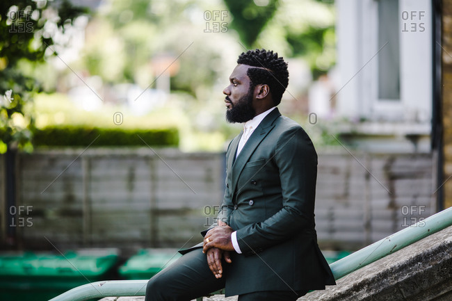 A side profile shot of a black man in a green suit sitting on a stairs railing