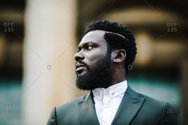 A side profile close up shot of a serious black man in a green suit