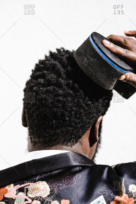 A close up shot from behind of a black man while he brushes his hair