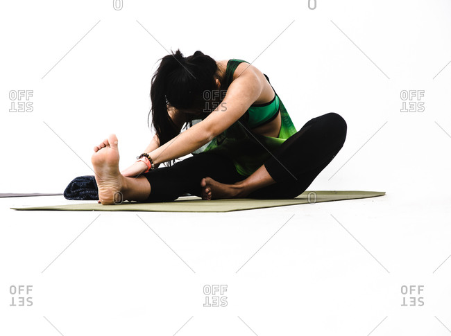 Wide shot of a woman stretching out her leg on a yoga mat