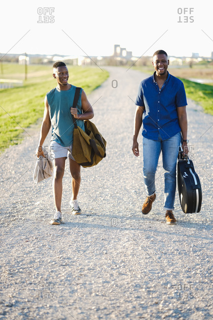 Two men walking on an empty road holding bag and guitar