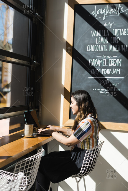 Vertical portrait of an Asian woman sitting in bright sunlight at her desk and working on her laptop