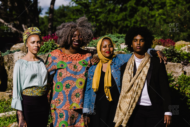 A group of three happy black Muslim women and a young black man standing together