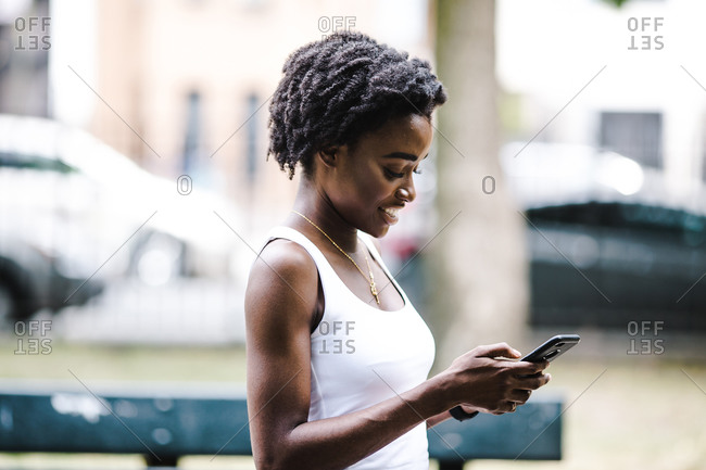 Side view of a woman glancing down at her phone while standing outdoors