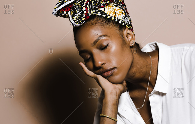 Portrait of woman wearing a colorful head scarf with a tired expression against a brown wall