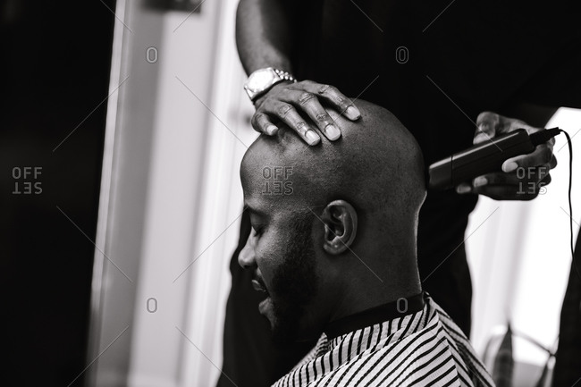 Black and white shot of a barber shaving a male client's head using a trimmer
