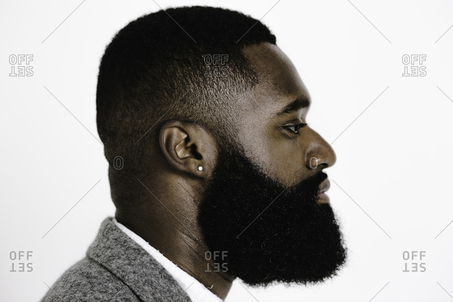 Side profile of a man with a beard dressed in a grey suit