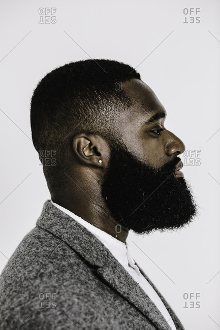 Vertical shot of the side profile of a man with a beard dressed in a grey suit