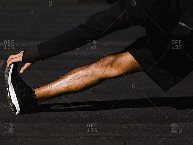 Man in a hoodie stretches out his leg on a pavement
