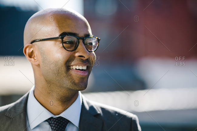 Portrait of a bald black man in a suit and glasses looking off into the distance and smiling