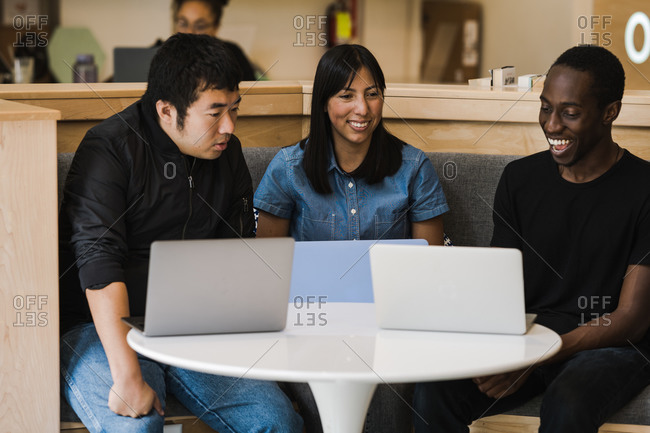 A medium shot of coworkers from different ethnic groups sitting at a table with their laptops