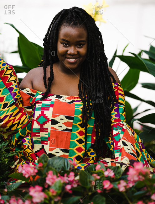 A portrait shot of a happy black woman in a colorful African dress with long braids surrounded by flowers