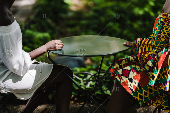 A medium shot of two black women from neck down sitting at a table outside