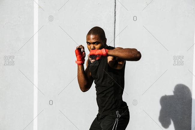 Black boxer performing a jabbing exercise in front of a grey wall