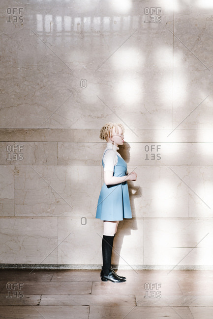 Vertical full length profile shot of a woman in a turtle neck blue dress and black socks standing in front of a wall