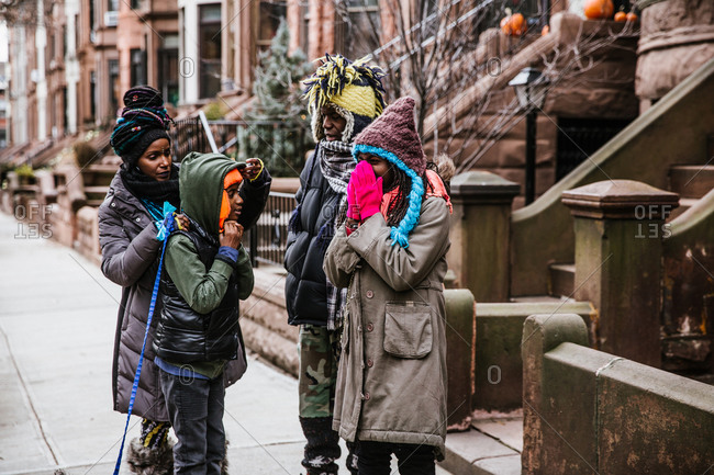 A medium shot of a black family standing outside on the street in winter clothing