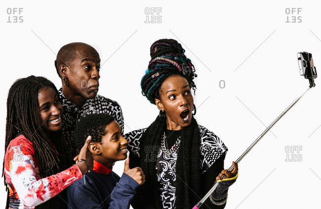 A medium shot of a happy african American family in african clothing taking photo with a selfie stick