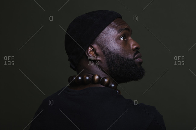 A close up back shot of a serious African American man wearing a black beanie cap posing with a big beads necklace against a green background