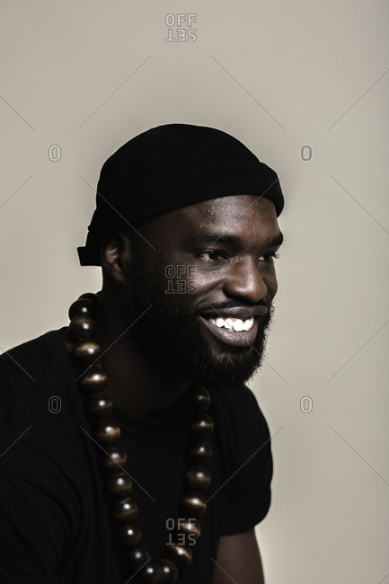 A side profile portrait shot of a happy African American man with beard wearing a black beanie cap posing with a big beads necklace