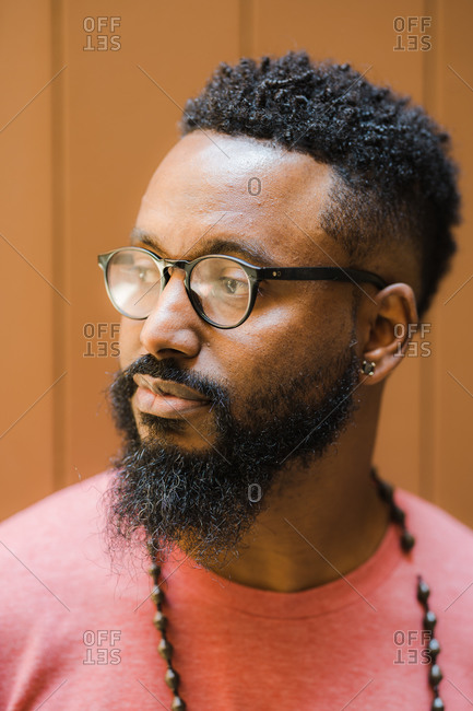 Vertical head and shoulder portrait of a black man in tshirt wearing glasses, earrings and necklace in front of a brown paneled wall