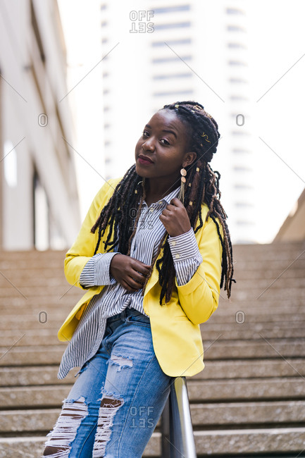 Vertical portrait of a stylish girl with long braids leaning on a railing