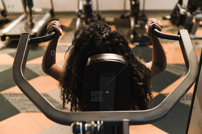 Rear view of a Black woman working out on shoulder press machine in the gym