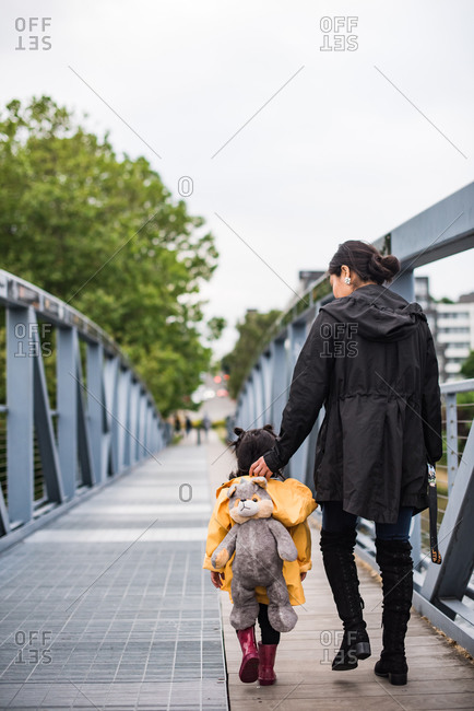 Native American woman walking along a bridge with her daughter