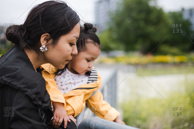 Wide shot of a mother and daughter looking at something on the ground