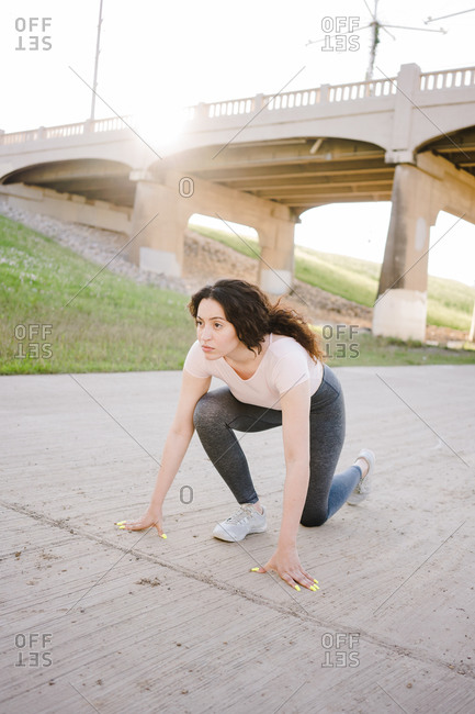 Vertical portrait of a woman taking position to sprint on an empty road